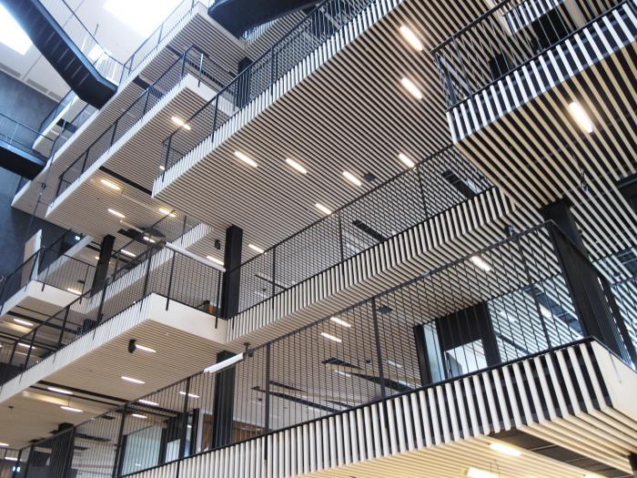 I det store atrium midt i bygningskroppen spiller lyse trælister en væsentlig rolle.  trælister spiller en væstetlig rolle